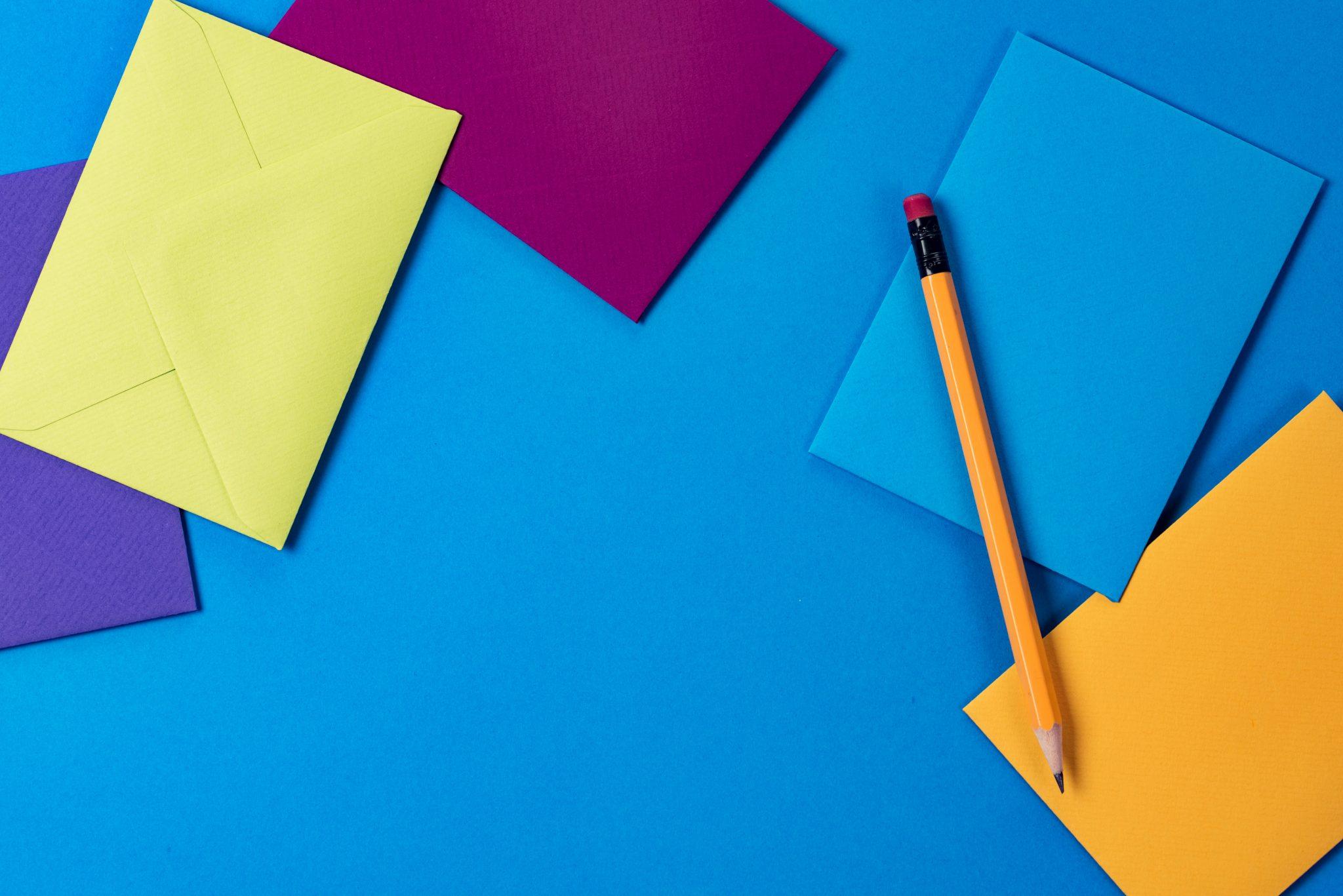 Penna, brev och papper på blå bakgrund.